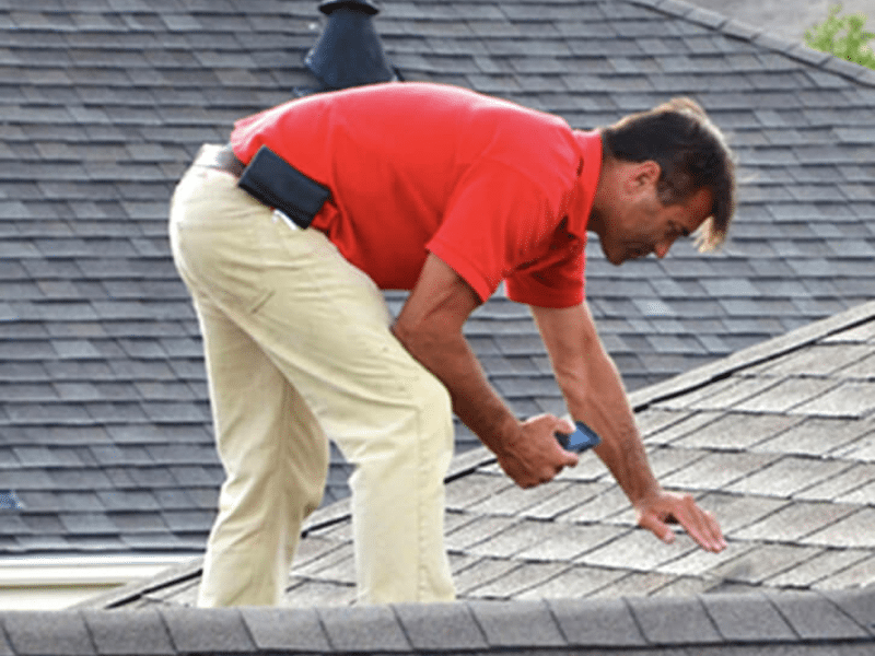 Roofing contractor performing an inspection on a roof