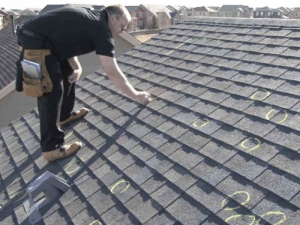 Roofing contractor inspecting roof damage