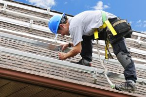 Roofing contractor installing new asphalt shingles
